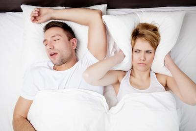 Man Snoring and Woman holding pillow over ears | Dentist in Pascoe Vale
